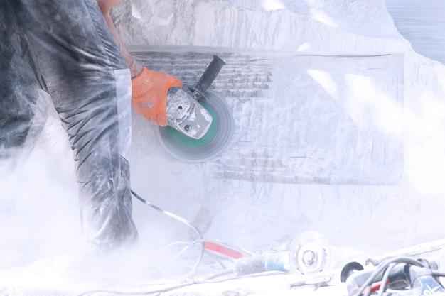 Un homme travaille sur un monument de pierre blanche. travaux de broyage. Photo Premium