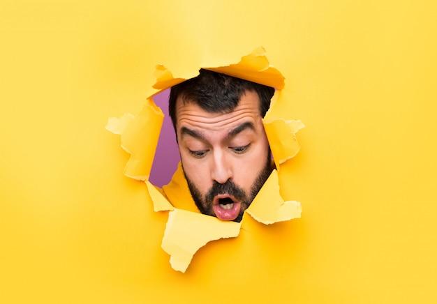Homme à travers un trou de papier faisant un geste de surprise Photo Premium