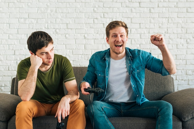 Homme triste regardant un ami heureux applaudir après avoir remporté le jeu vidéo Photo gratuit