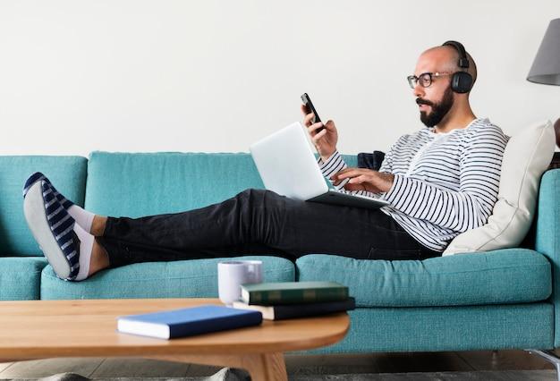 Homme utilisant un appareil sur un canapé Photo Premium