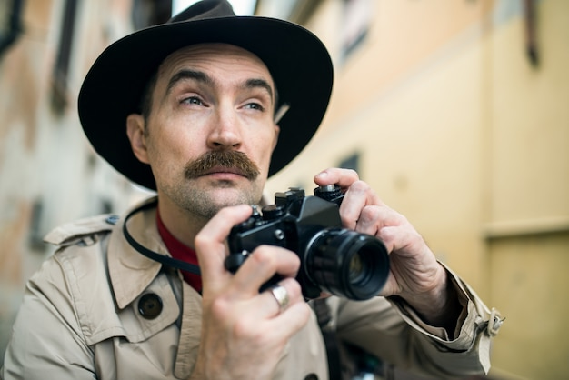 Homme utilisant un appareil photo vintage dans une rue de la ville Photo Premium