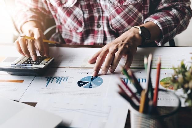 Homme utilisant une calculatrice tout en travaillant pour des documents financiers Photo Premium