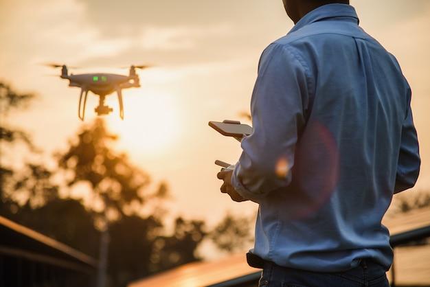 Homme utilisant un drone avec télécommande, pilotage de drone au coucher du soleil Photo Premium