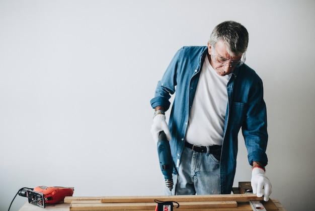 Homme utilisant un foret à main avec une planche Photo Premium