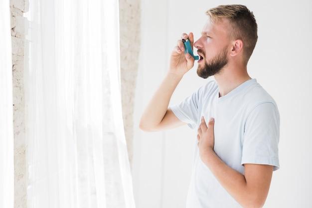 Homme utilisant un inhalateur pour l'asthme Photo gratuit