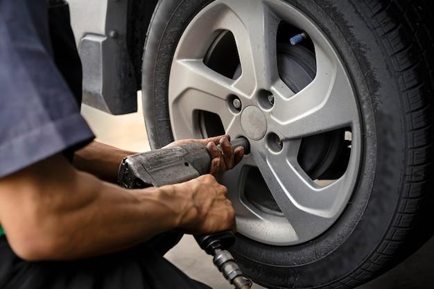 Homme utilisant un mécanicien automobile bloquez la roue éolienne. pour vérifier vos pneus et vos freins pour voiture. mécanicien automobile préparation au travail. Photo Premium
