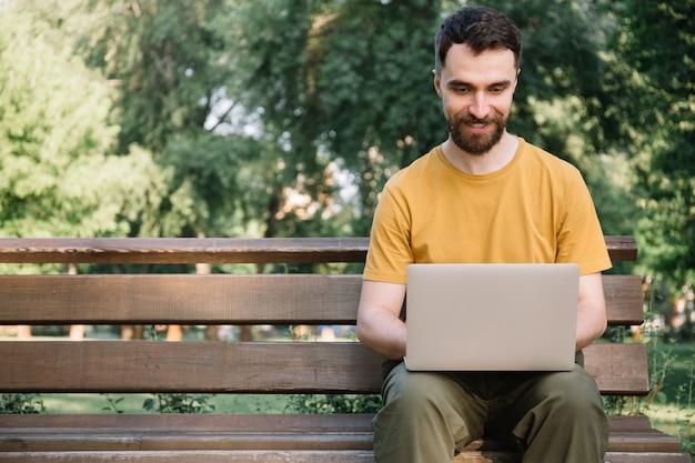Homme Utilisant Un Ordinateur Portable, Assis Sur Un Banc. Freelancer Travaillant Dans Le Parc, En Tapant Sur Le Clavier Photo Premium