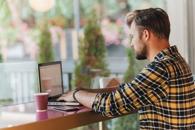 Homme utilisant un ordinateur portable dans un café Photo gratuit