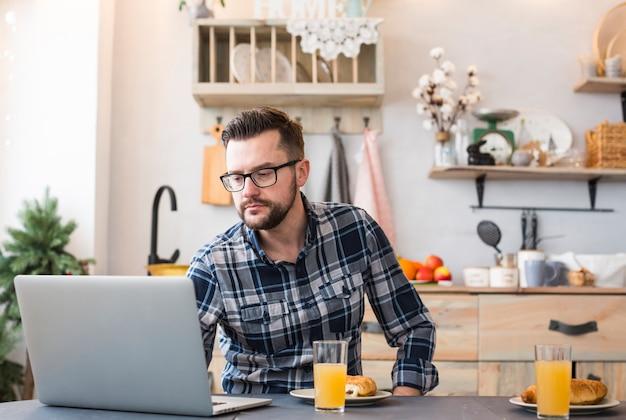 Homme utilisant un ordinateur portable à la table du petit déjeuner Photo gratuit