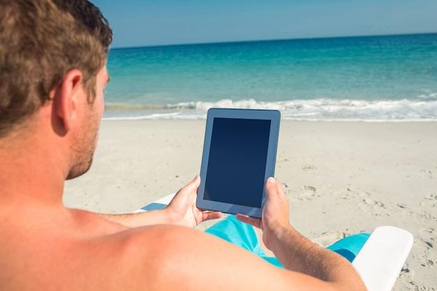 Homme utilisant une tablette numérique sur une chaise longue à la plage par une journée ensoleillée Photo Premium