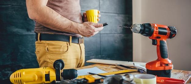 Homme utilisant un téléphone intelligent et tenant une tasse de café Photo Premium