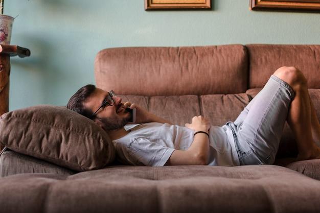Homme utilisant un téléphone portable en position couchée sur un canapé à la maison Photo Premium