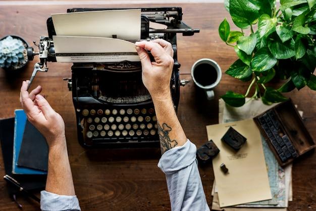 Homme utilisant le travail de machine à écrire rétro machine writer changer de papier Photo Premium