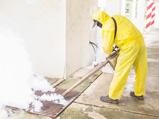 L'homme utilise une machine à brouillard thermique pour empêcher la propagation des moustiques Photo gratuit
