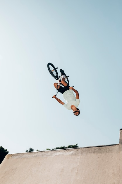 Homme sur un vélo de bmx effectuant un saut dans un skatepark Photo gratuit