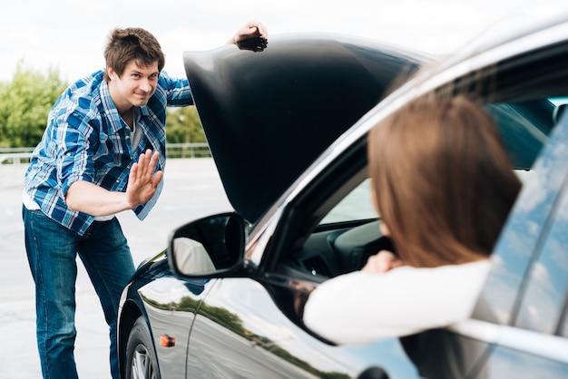 Homme vérifiant le moteur et la femme assise dans la voiture Photo gratuit