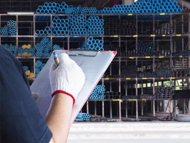 Un homme vérifie les tuyaux et les aciers en pvc dans un entrepôt. Photo Premium