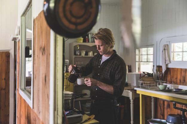 Homme versant du café dans la cuisine sur un vieux chalet en bois Photo Premium