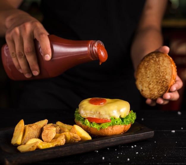 Homme versant du ketchup sur un burger de bœuf savoureux Photo gratuit