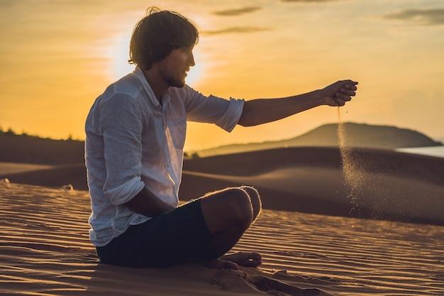 Un Homme Verse Du Sable Dans Le Désert. Poncez Entre Les Doigts Du Concept. Photo Premium
