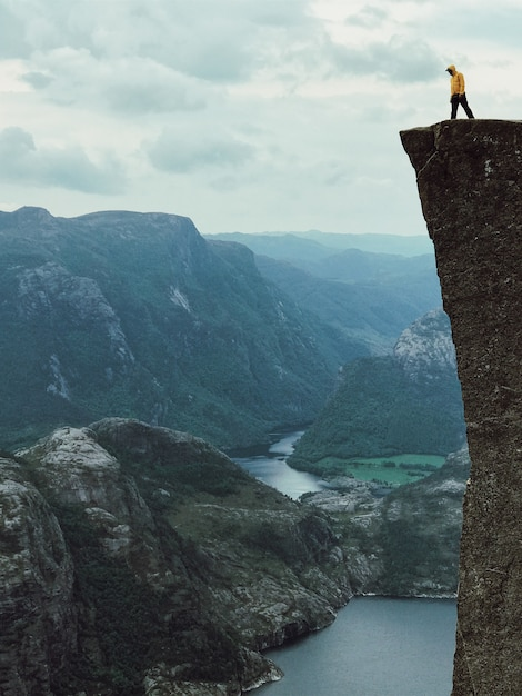 L'homme avec une veste jaune pose sur le sommet de la roche Photo gratuit