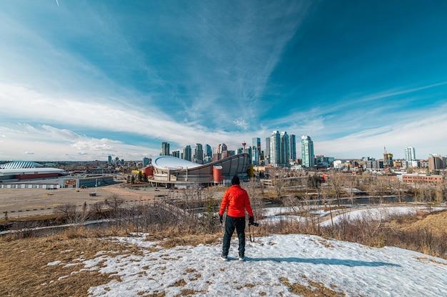 Homme Avec Une Veste Rouge Regardant La Ville De Calgary En Alberta, Canada Photo Premium
