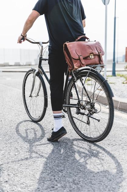 Homme en vêtements noirs, faire du vélo sur route Photo gratuit