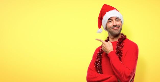 Homme avec des vêtements rouges célébrant les vacances de noël pointant vers le côté Photo Premium