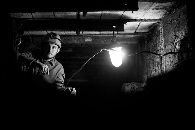 Un Homme Vêtu D'une Combinaison De Protection Et D'un Casque Est Assis Dans Un Tunnel Avec Un Album En Feu. Mineur Dans Le Mien Photo Premium