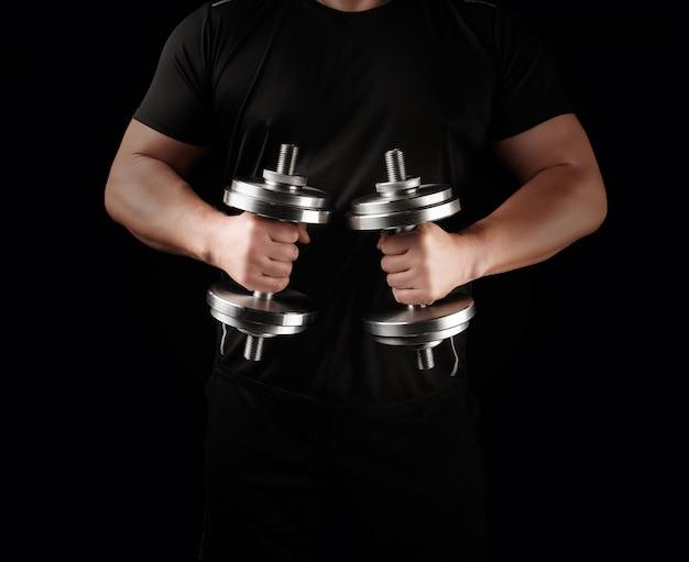 Un homme vêtu de noir tient des haltères en acier dans ses mains, ses muscles sont tendus Photo Premium