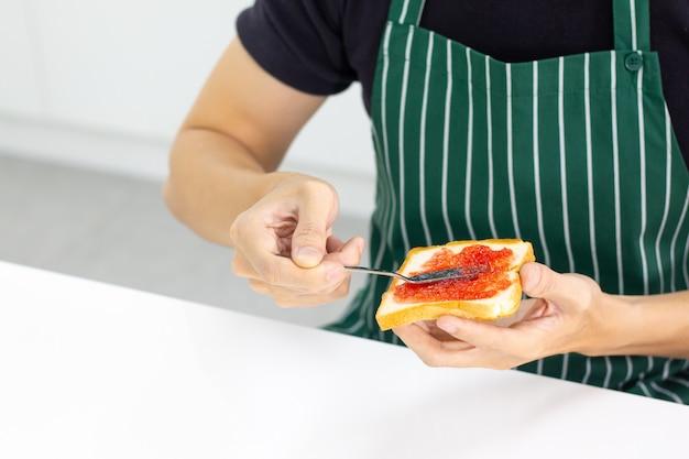 Homme vêtu d'un tablier rayé vert assis dans la salle de cuisine Photo Premium
