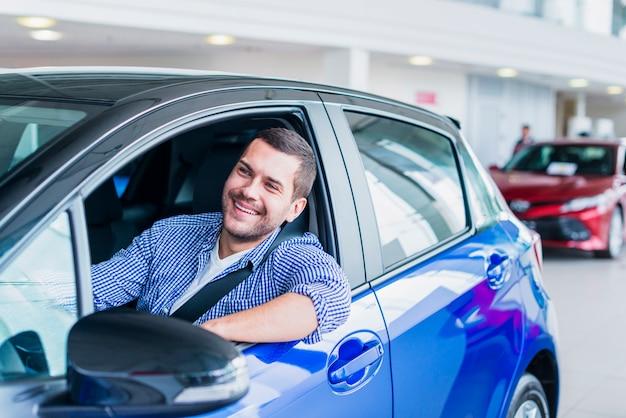Homme en voiture chez un concessionnaire Photo gratuit