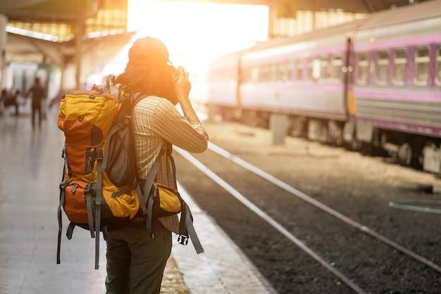 L'homme voyageur attend le train sur le quai Photo Premium