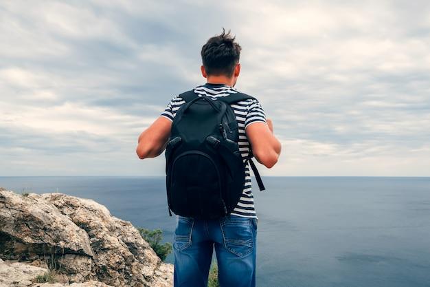 Homme voyageur avec sac à dos à la recherche de la mer Photo Premium