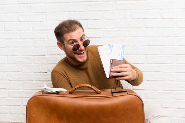 Homme voyageur avec valise et carte d'embarquement et tenant un avion en jouet Photo Premium