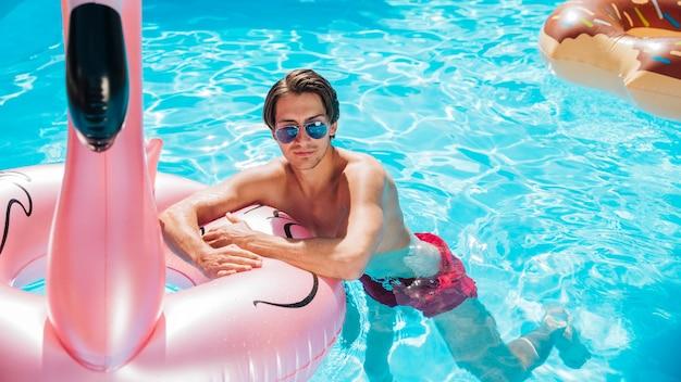 Homme vue de face sur l'anneau de bain flamant rose Photo gratuit