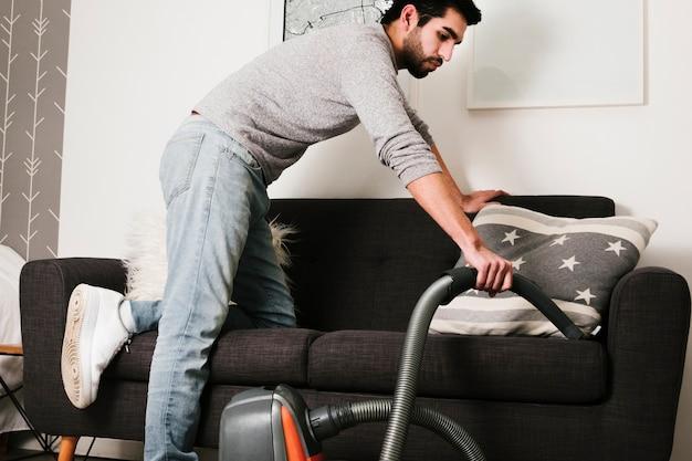 Homme vue de face aspirer un canapé Photo gratuit