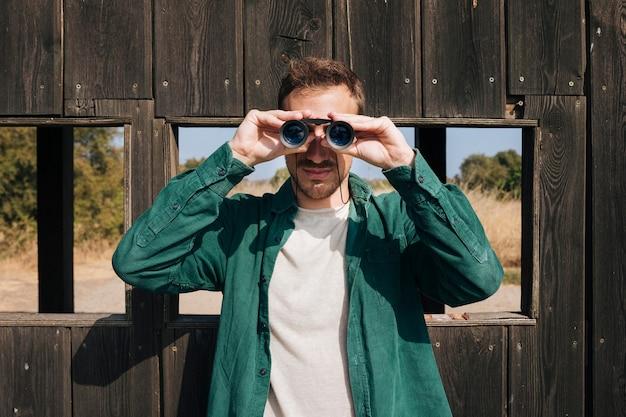Homme vue de face à la recherche à travers des jumelles Photo gratuit