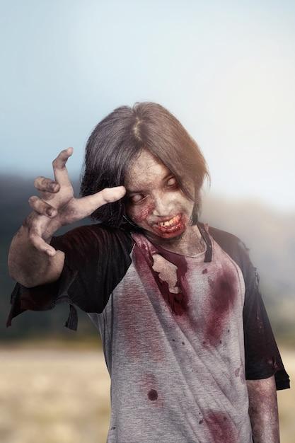 Homme de zombie effrayant avec griffe des mains debout en plein air Photo Premium