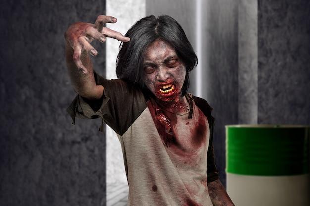 Homme de zombie effrayant avec les mains pour griffer sur l'endroit sombre Photo Premium