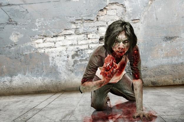 Homme zombie fantasmagorique mangeant de la viande crue Photo Premium