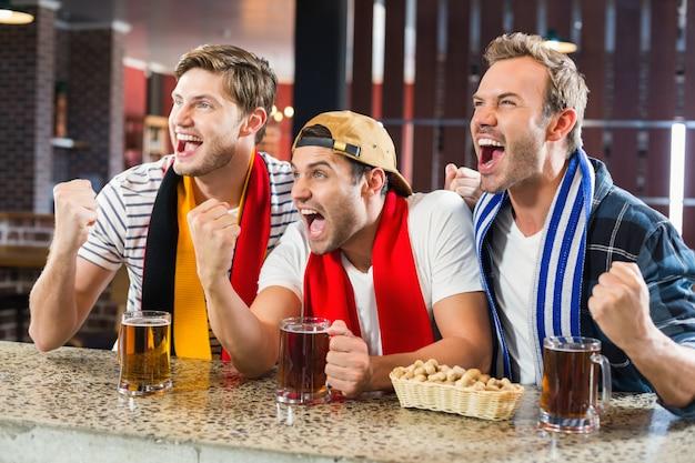 Hommes acclamant avec des bières Photo Premium