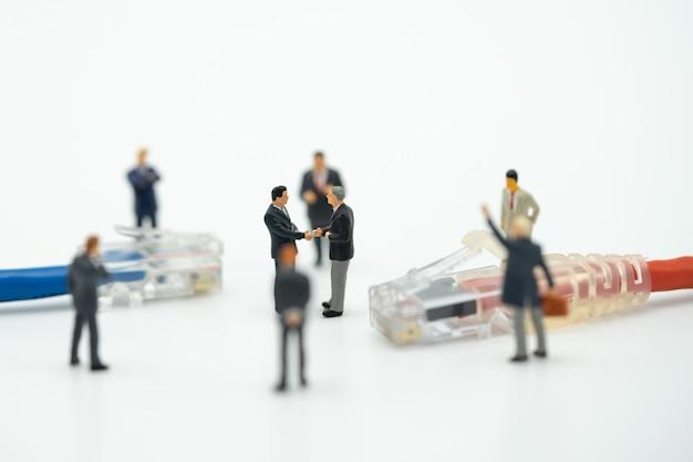 Hommes d'affaires 2 personnes miniatures serrer la main dans le dos négocier en entreprise. Photo Premium