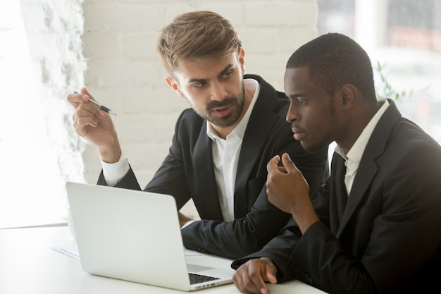 Hommes D'affaires Africains Et Caucasiens Discutant Idée De Projet En Ligne Avec Ordinateur Photo gratuit