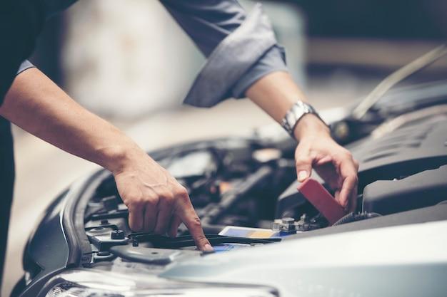 Des hommes d'affaires aident les femmes d'affaires à vérifier et réparer les voitures en panne Photo Premium
