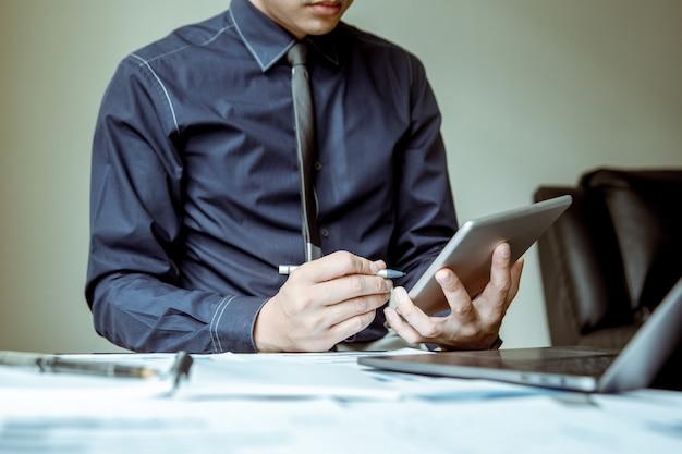 Les hommes d'affaires asiatiques utilisent des tablettes et des stylos pour analyser l'économie. Photo Premium