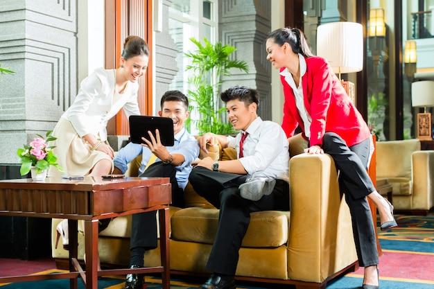 Hommes d'affaires chinois d'origine asiatique réunis dans le hall de l'hôtel Photo Premium
