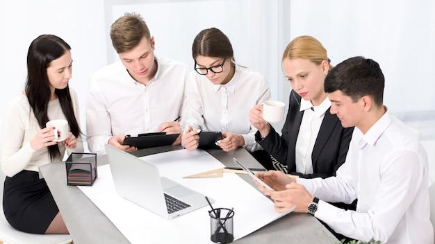 Hommes d'affaires créatifs avec mobile; ordinateur portable et tablette numérique travaillant ensemble au bureau Photo gratuit