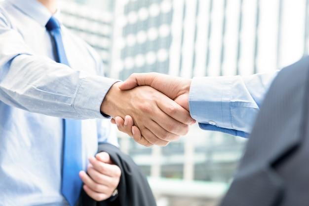 Hommes d'affaires faisant la poignée de main à l'extérieur en face d'immeubles de bureaux dans la ville Photo Premium