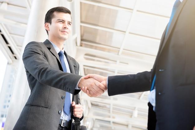 Hommes d'affaires faisant une poignée de main sur une passerelle couverte en plein air Photo Premium